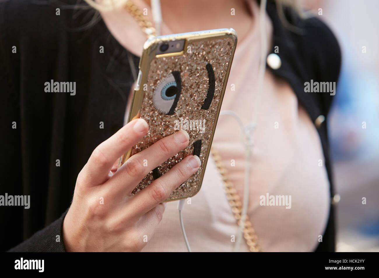 Frau mit goldenem Glitzer Smartphone Hülle mit Augen vor Salvatore Ferragamo Modenschau, Milan Fashion Week Stockbild