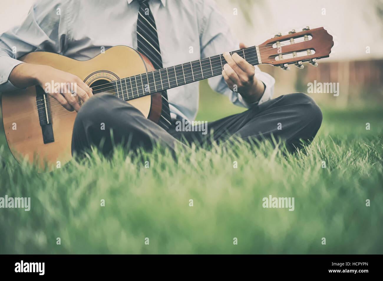 Junger Mann, die Gitarre zu spielen, auf der Wiese Stockbild