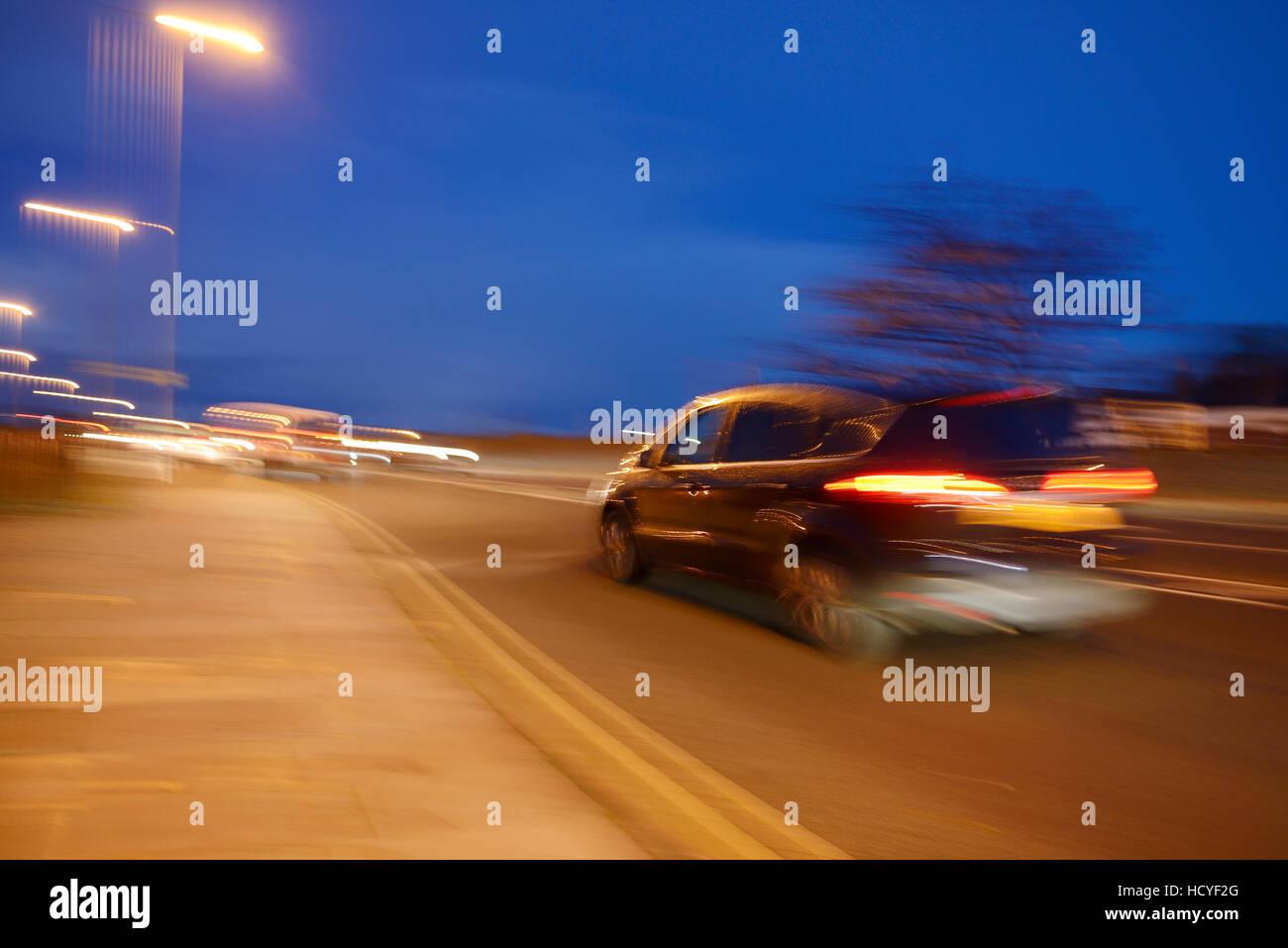 Verschwommene Verkehr auf eine städtische Straße in der Abenddämmerung Stockbild