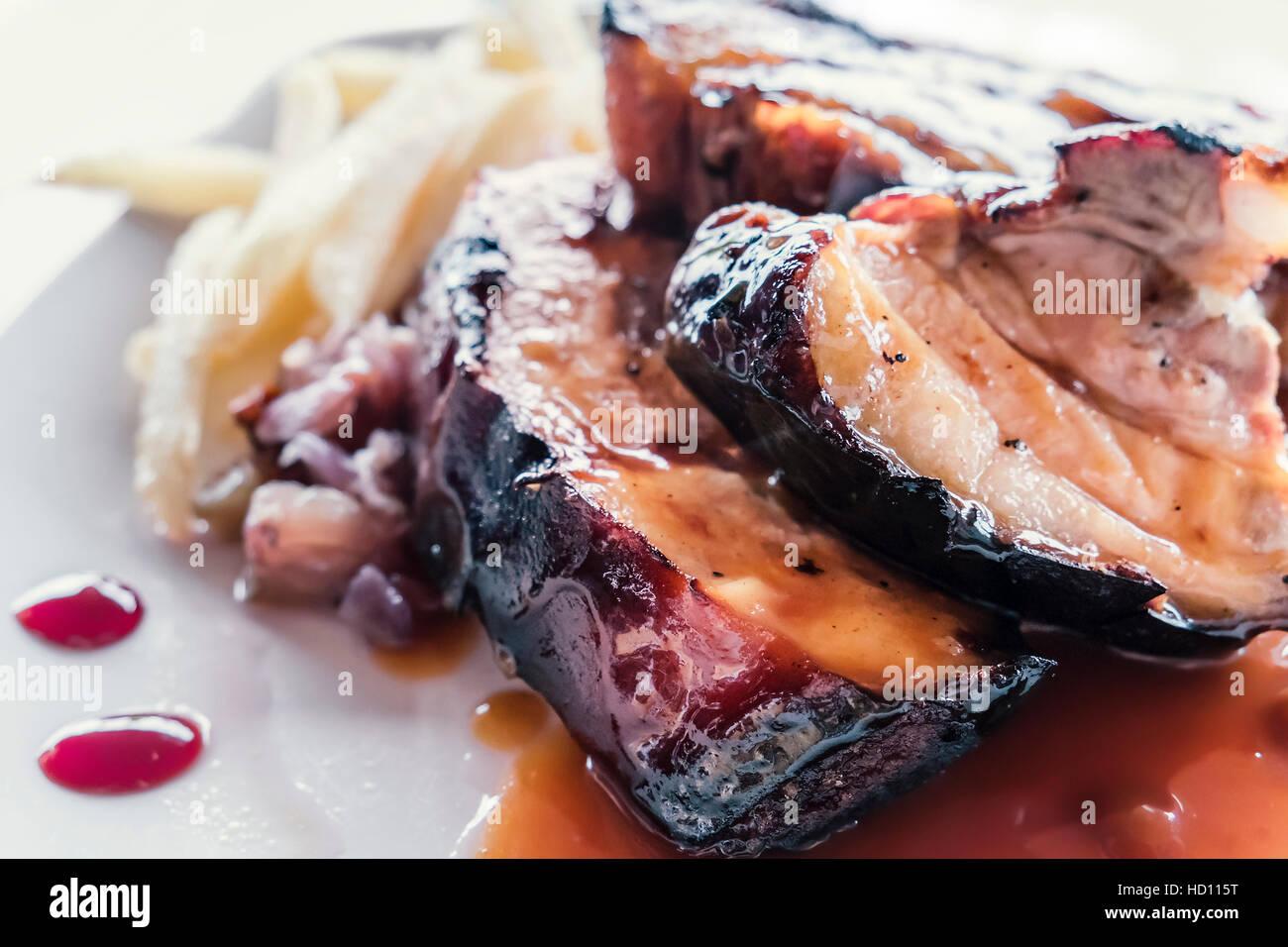 Spanisch Spareribs, entbeint und mit roten Honig Dip und Pommes frites als Beilage serviert. Stockbild