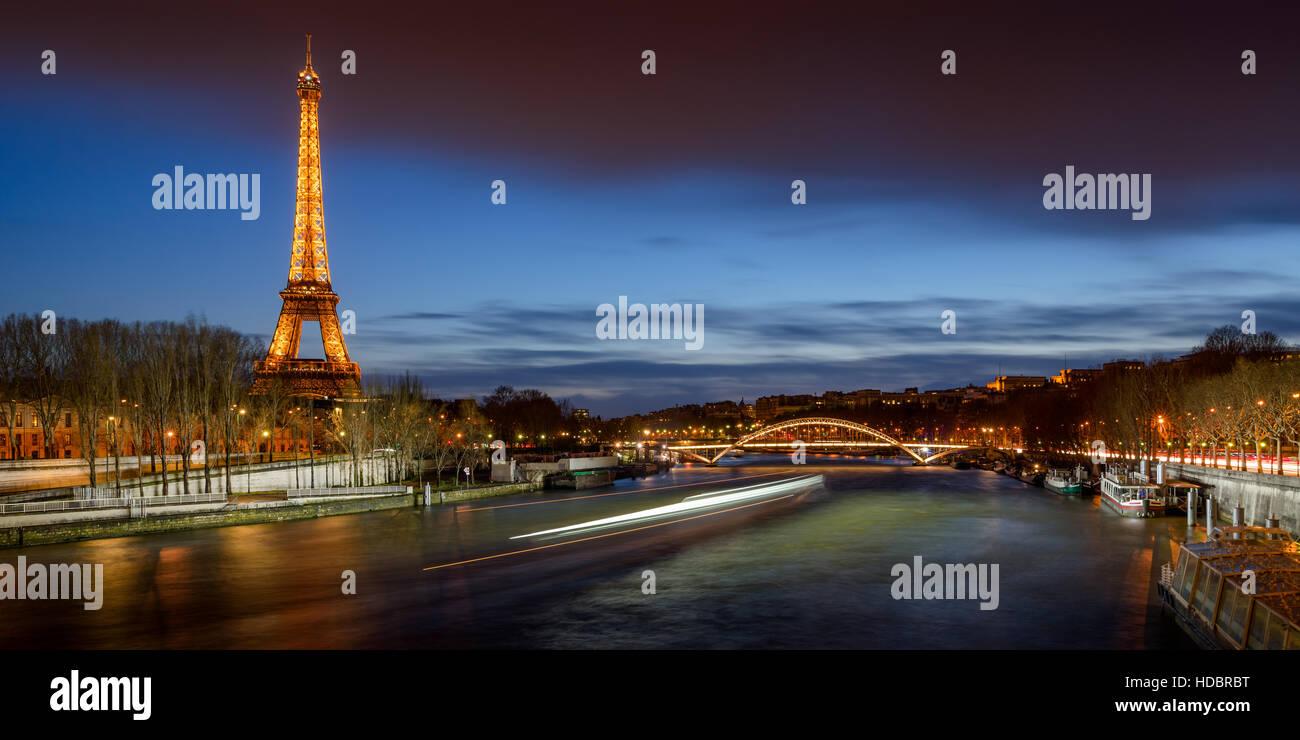 Der Eiffelturm in der Dämmerung mit den Ufern des Flusses Seine und die Passerelle Debilly beleuchtet. Paris, Stockbild