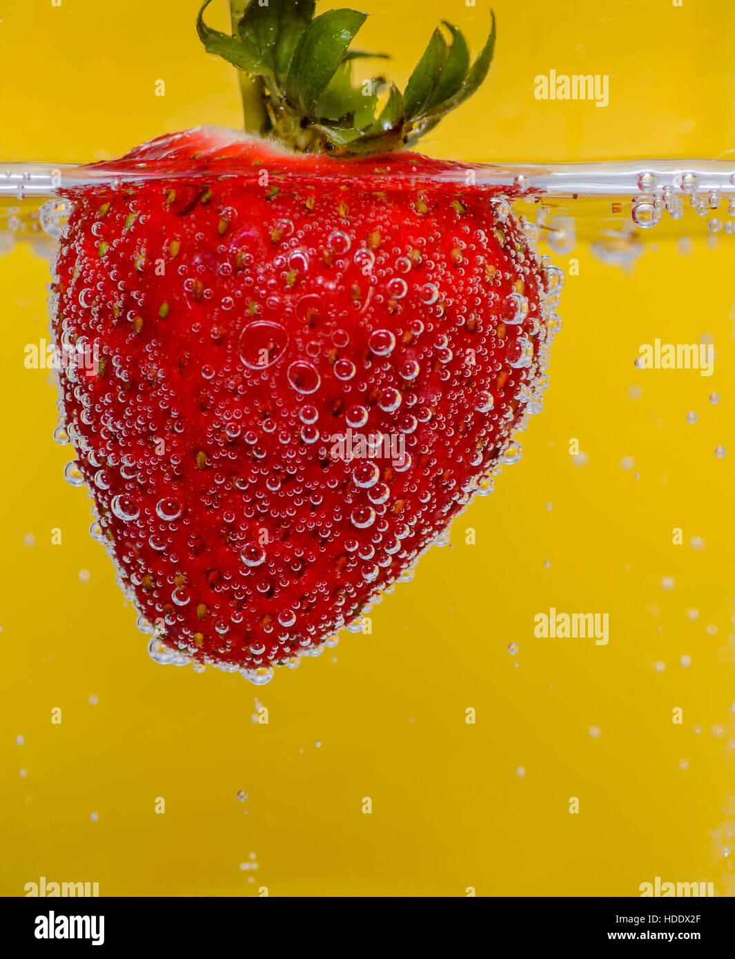 Erdbeere im Mineralwasser vor einem gelben Hintergrund Stockbild