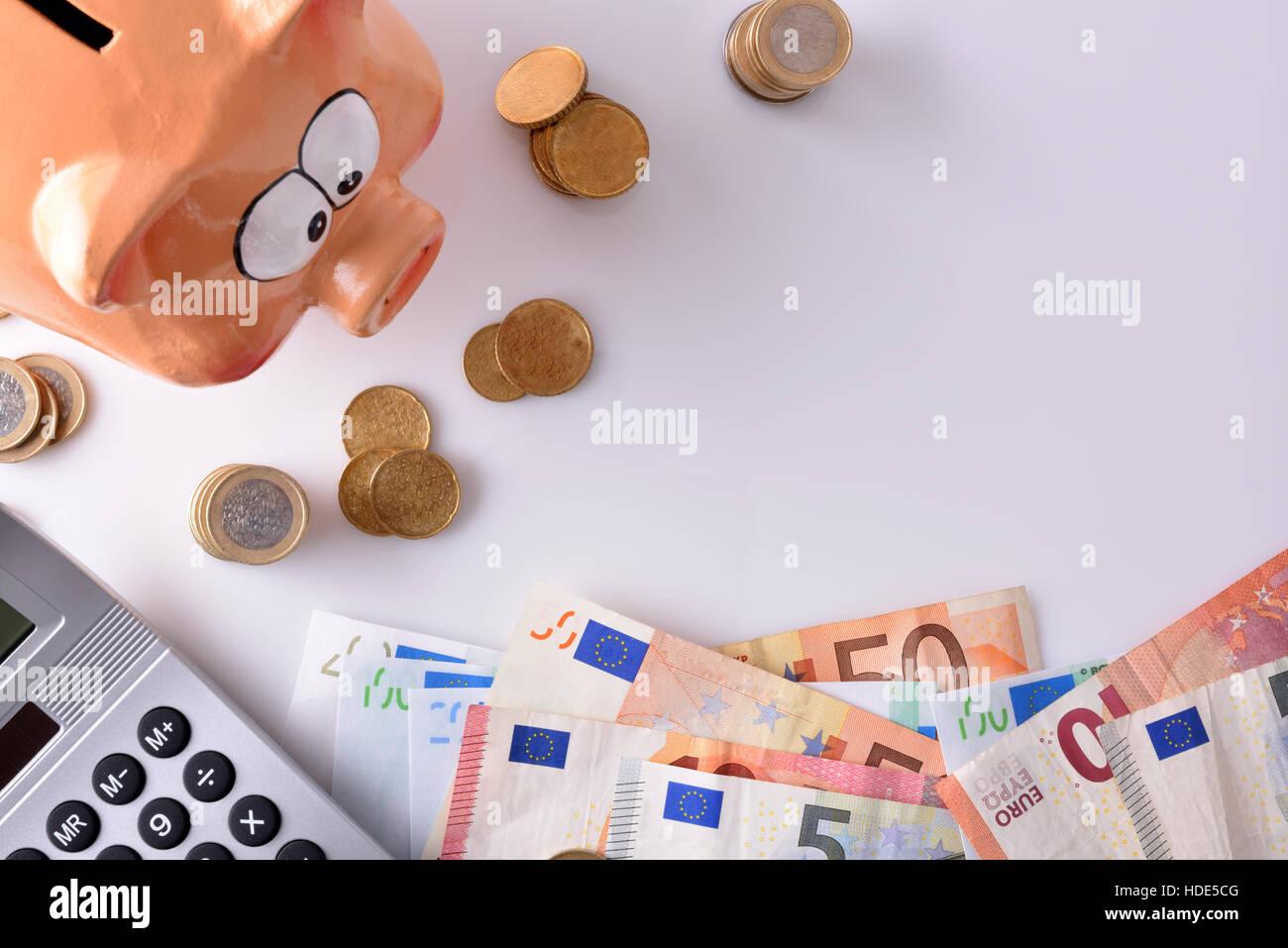 Konzept-Einsparungen und Buchhaltung mit Sparschwein und gestapelten Münzen und Rechnungen und Rechner auf Stockbild