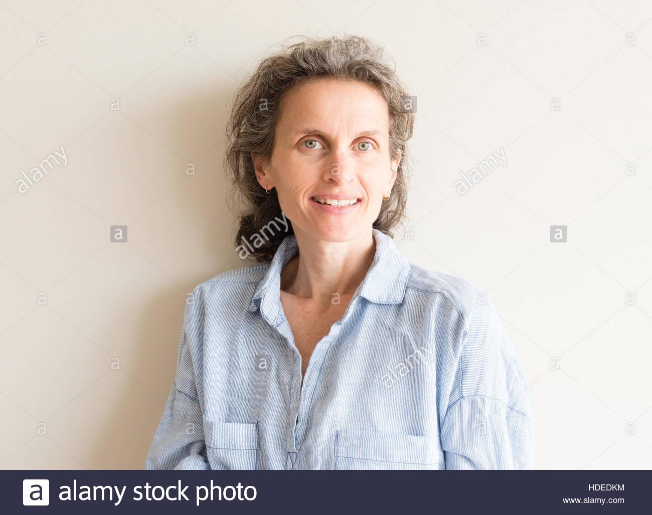 Natürlich aussehende mittlere gealterte Frau mit grauen Haaren und blauen Hemd lächelnd Stockbild