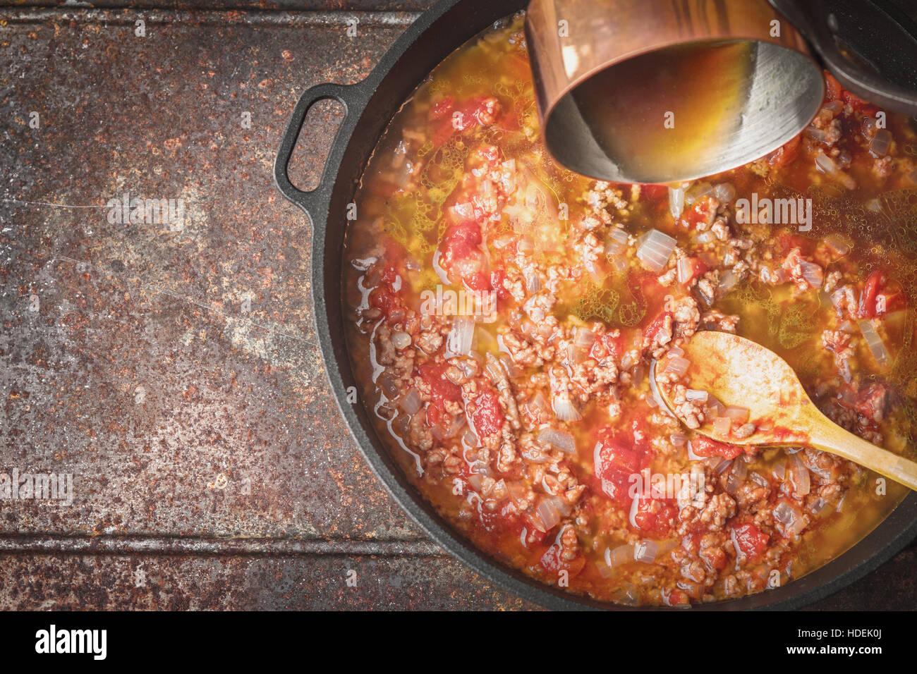 Schmoren von Fleisch, Draufsicht Zwiebeln und Tomaten Stockbild