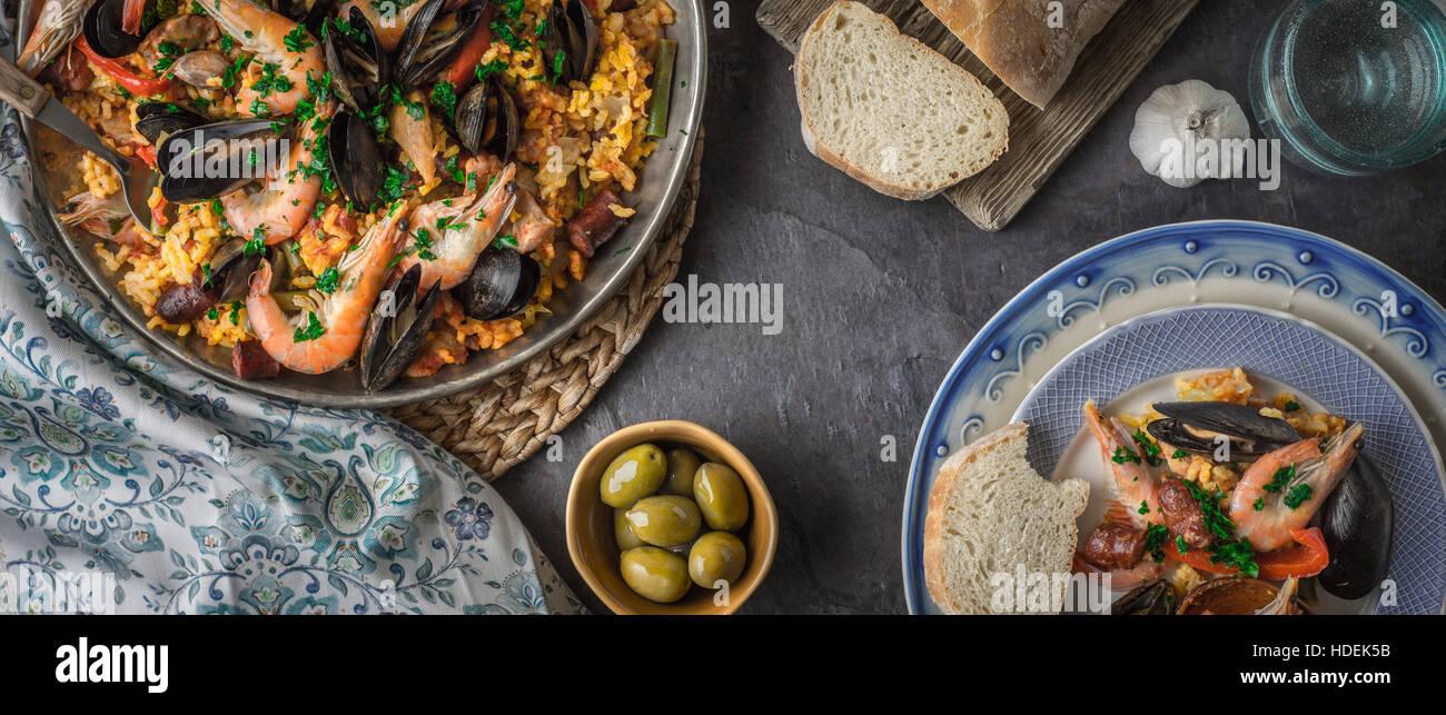 Platten mit Paella auf dem dunklen Stein Tisch mit verschiedenen Accessoires Breitbild Stockbild