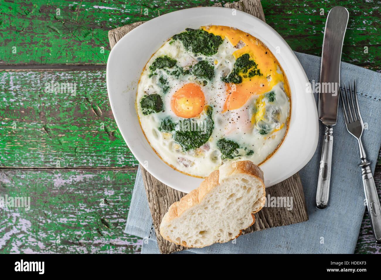 Florentiner Eiern mit pürierten Spinat auf dem Holztisch horizontale Stockbild