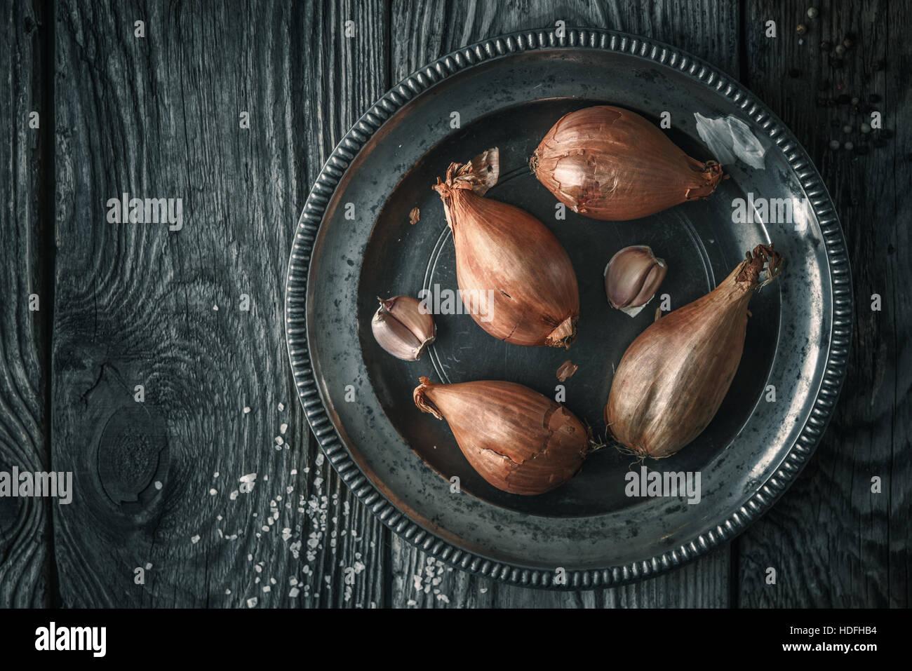 Schalotten in die Metallplatte auf der hölzernen Tischplatte-Ansicht Stockbild