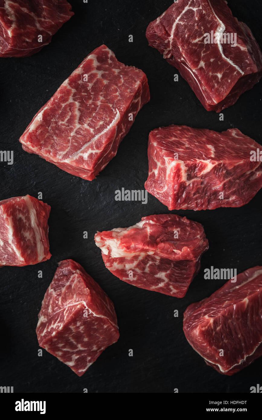 Rohe Angus-Rindfleisch-Scheiben auf den schwarzen Stein Tabelle vertikal Stockbild