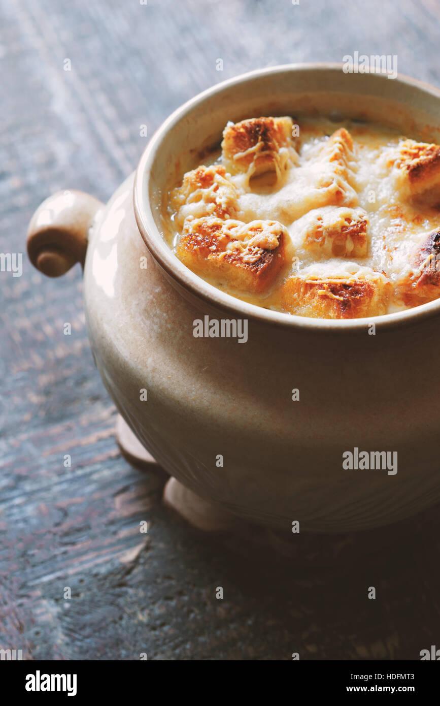 Zwiebelsuppe in Keramiktopf auf dem Holztisch vertikale Stockbild