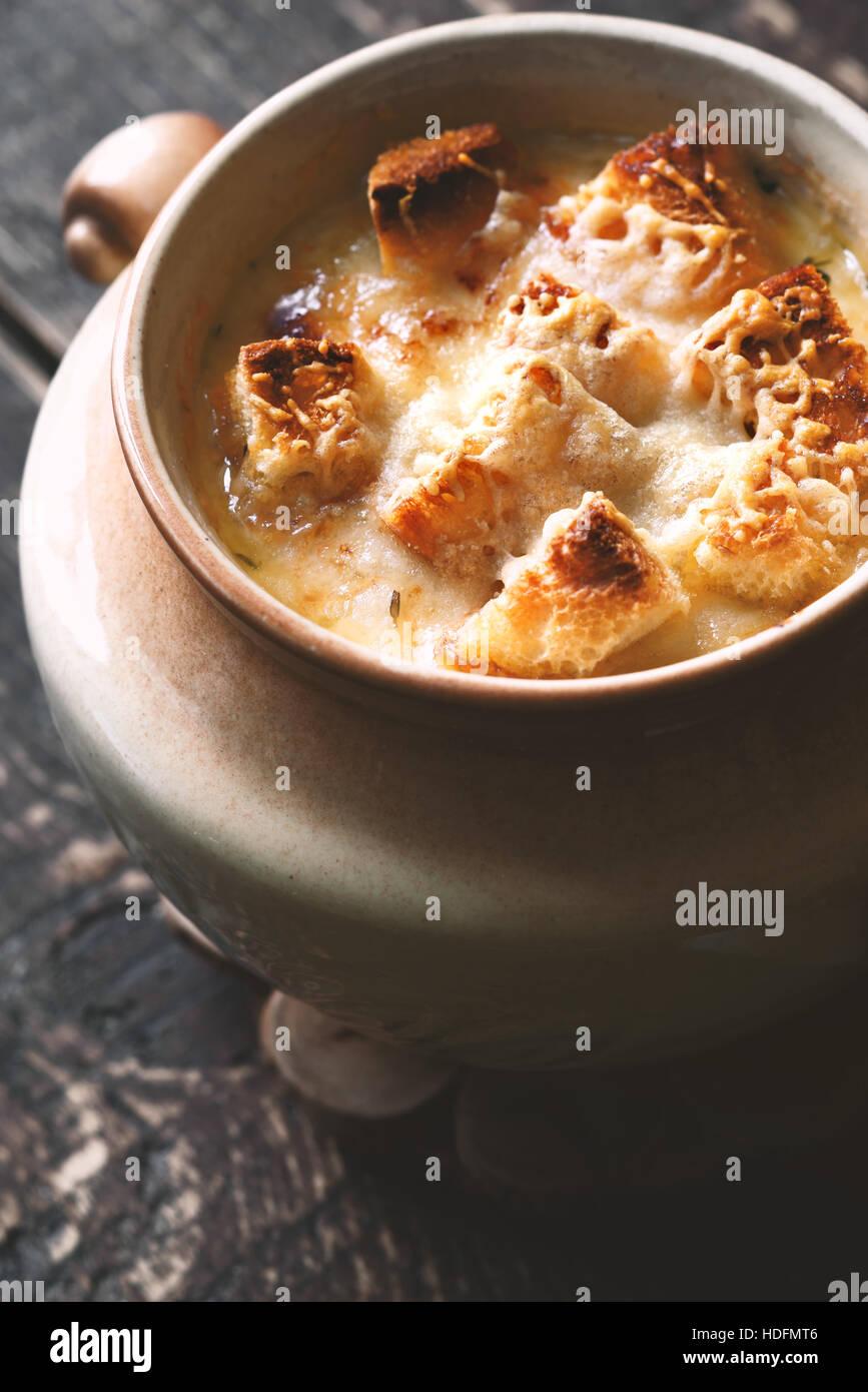 Zwiebelsuppe in Keramiktopf auf dem Holztisch Stockbild