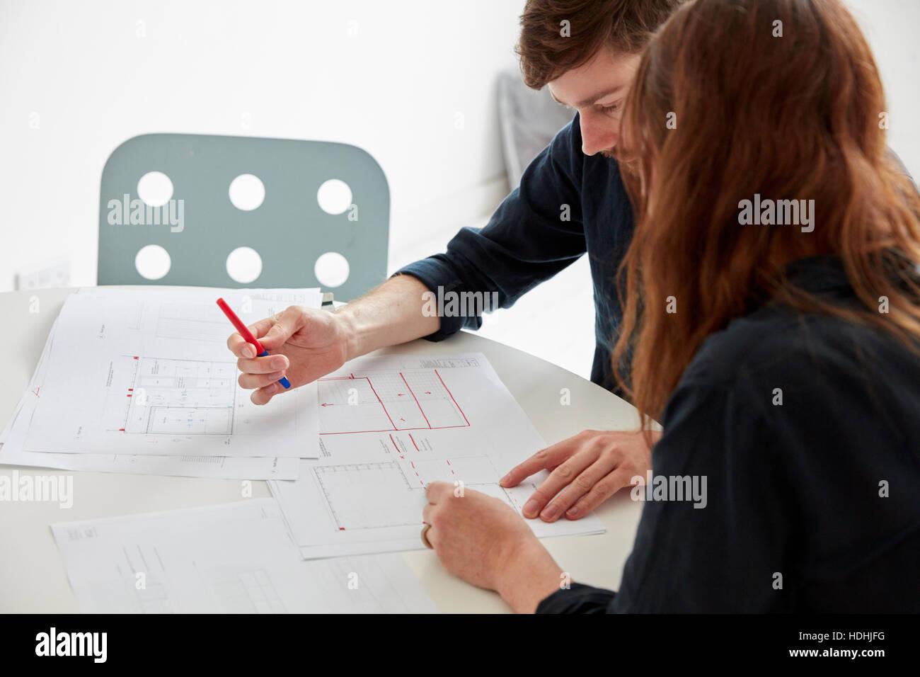 Ein modernes Büro. Zwei Menschen bei einem Treffen, diskutieren, Pläne und Zeichnungen, Architekturzeichnungen. Stockbild