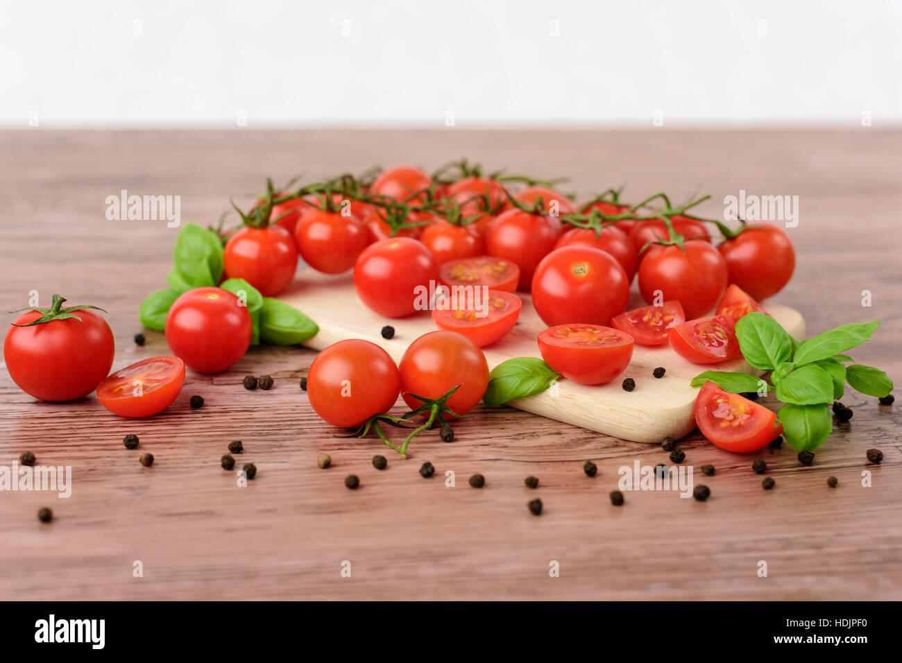 Mini-Tomaotes auf dem Holztisch mit hellem Hintergrund. Stockfoto