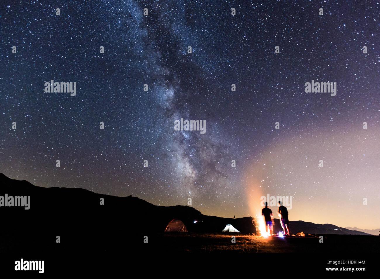 Milky Way. Nachthimmel mit Sternen und Silhouette des zwei-Mann um ein Feuer Stockfoto