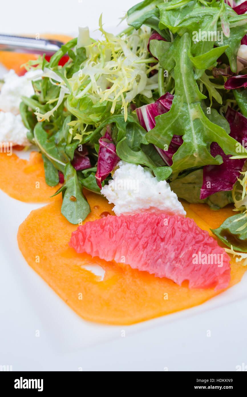 Nahaufnahme von einem Salat serviert mit Früchten und Ziege Käse mit einer Vielzahl von Salaten und einem Stockbild
