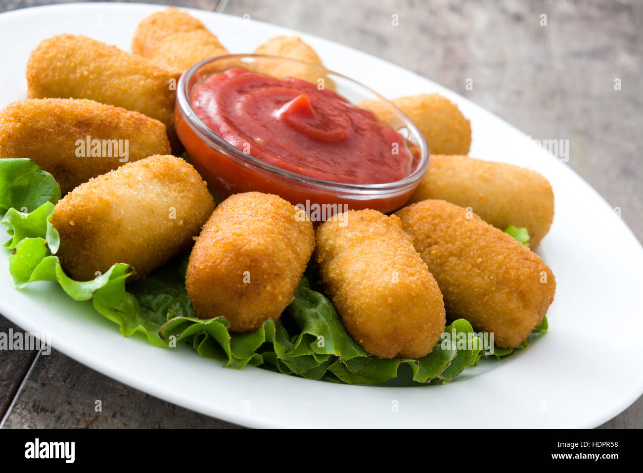traditionelle spanische croquetas kroketten mit ketchup in platte auf h lzernen hintergrund. Black Bedroom Furniture Sets. Home Design Ideas