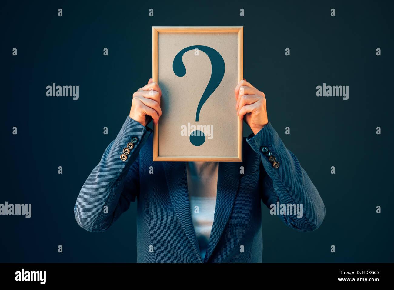 Geschäftsfrau mit Fragezeichen auf der Suche nach Antworten, Fragen und Gedanken über ungewisse Zukunft Stockbild