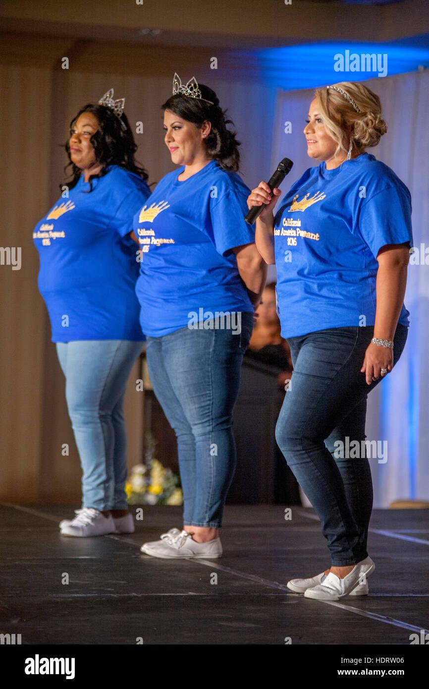 Afrikanisch-amerikanischen und kaukasischen plus Size Frauen singen auf der Bühne in einem Talentwettbewerb an Kalifornien Stockfoto