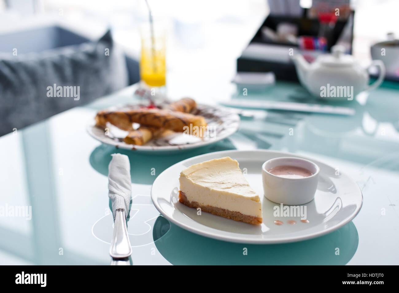 Stück Käsekuchen auf weißen Teller und Glas Tisch im café Stockbild