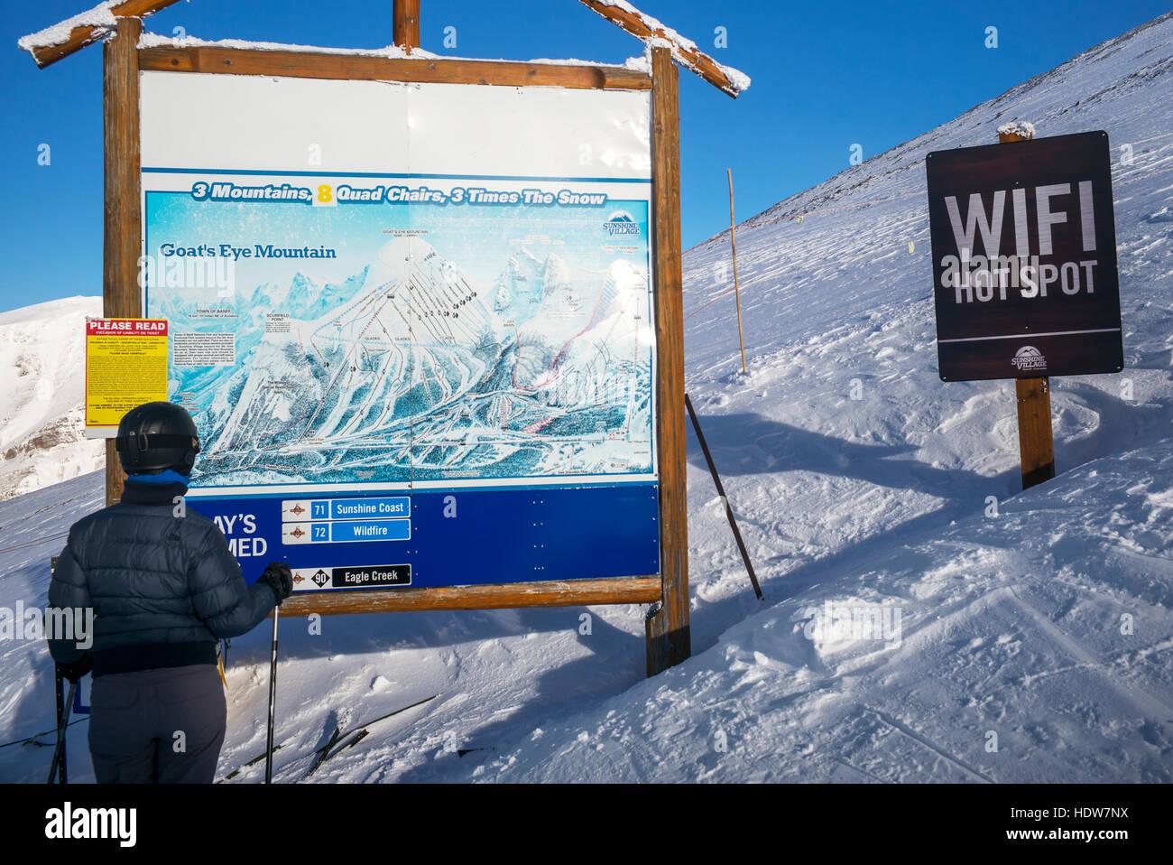 Ein Skifahrer steht Blick auf eine Karte des Skigebietes Sunshine Village mit einem WiFi-Hotspot Schild daneben Stockbild