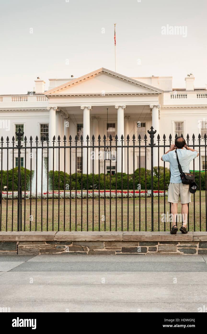 washington, dc - tourist späht durch das weiße haus vorgarten zaun