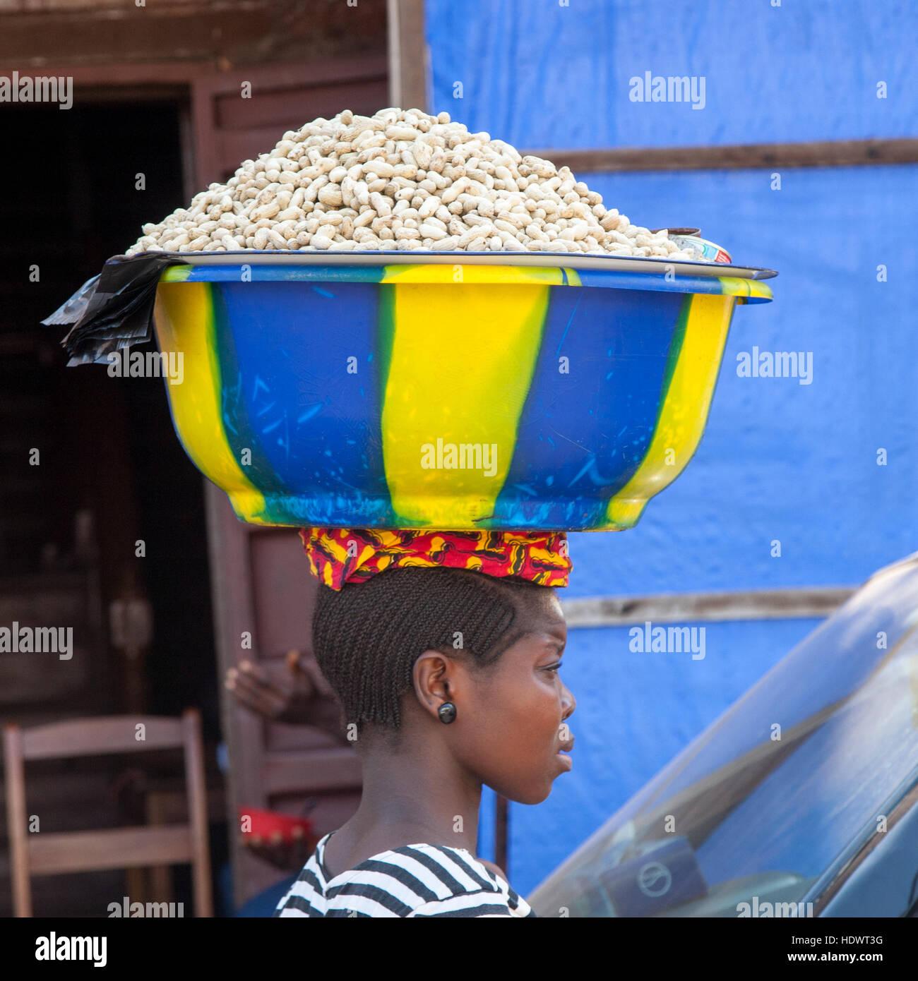 Afrikanische Frau trägt Schale mit Erdnüssen auf dem Kopf Stockfoto