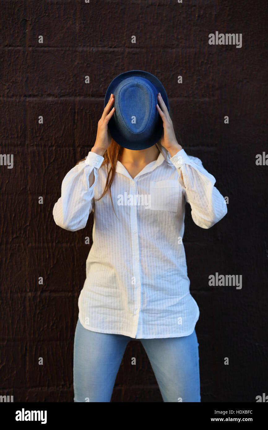 Fröhliches Mädchen mit Hut verbirgt ihr Gesicht Stockbild