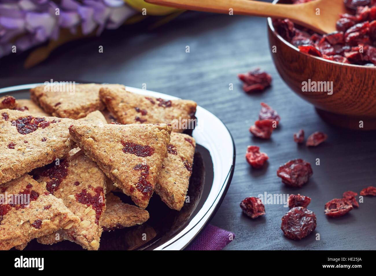 Vollkorn-Kekse mit getrockneten Cranberries auf schwarzem Hintergrund aus Holz Stockbild