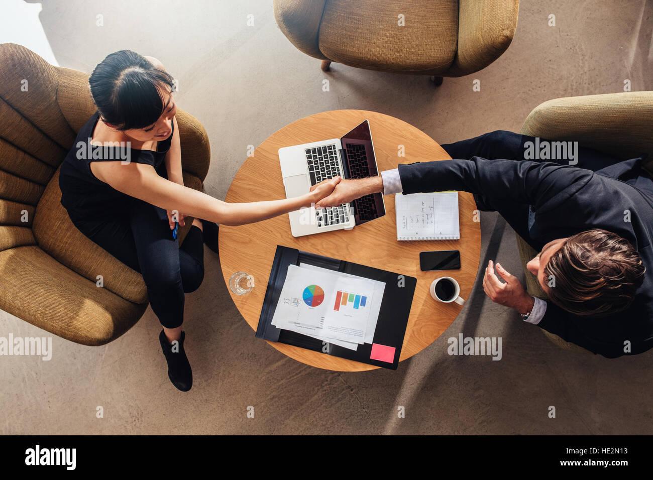 Draufsicht der jungen Geschäftspartner Händeschütteln auf Deal im Büro. Dokumente und Laptop Stockbild