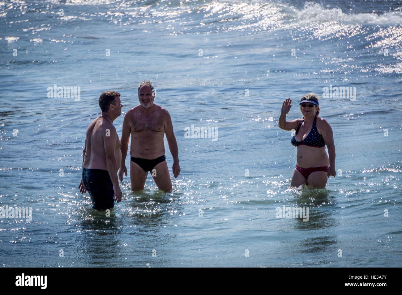 Zwei Männer mittleren Alters und Paddeln im Meer, die Frau in die Kamera winken Frauen Stockbild