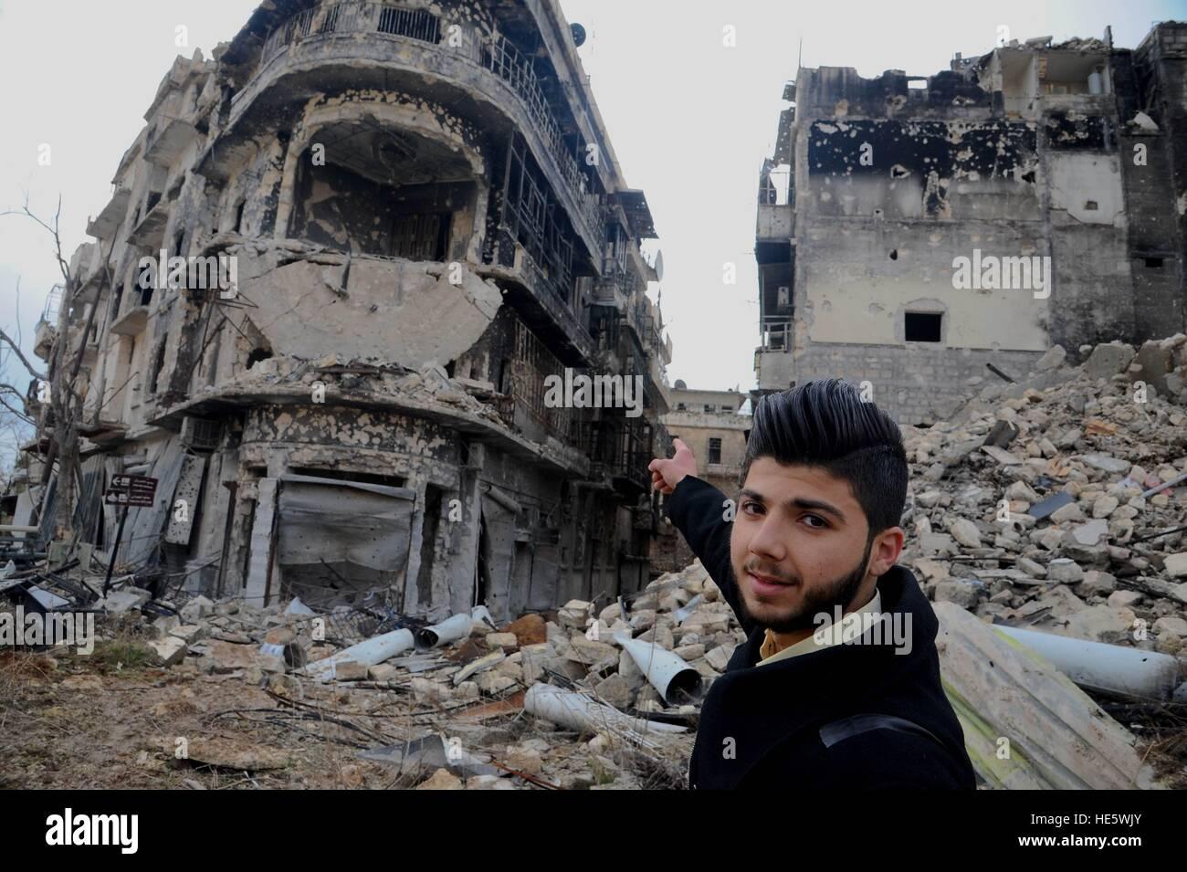 Aleppo, Syrien. 17. Dezember 2016. Ein Mann zeigt auf ein Gebäude, wo er zum Leben in der alten Stadt von Aleppo, Stockbild