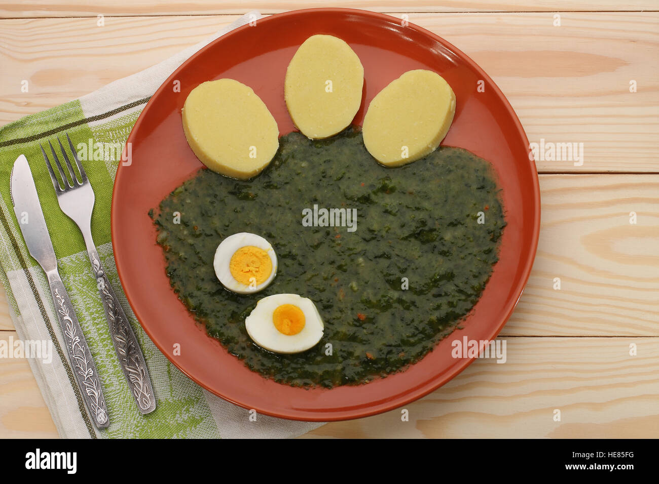 Spinat mit Kartoffelknödel und Spiegelei auf braune Teller mit Besteck auf Holztisch Stockbild