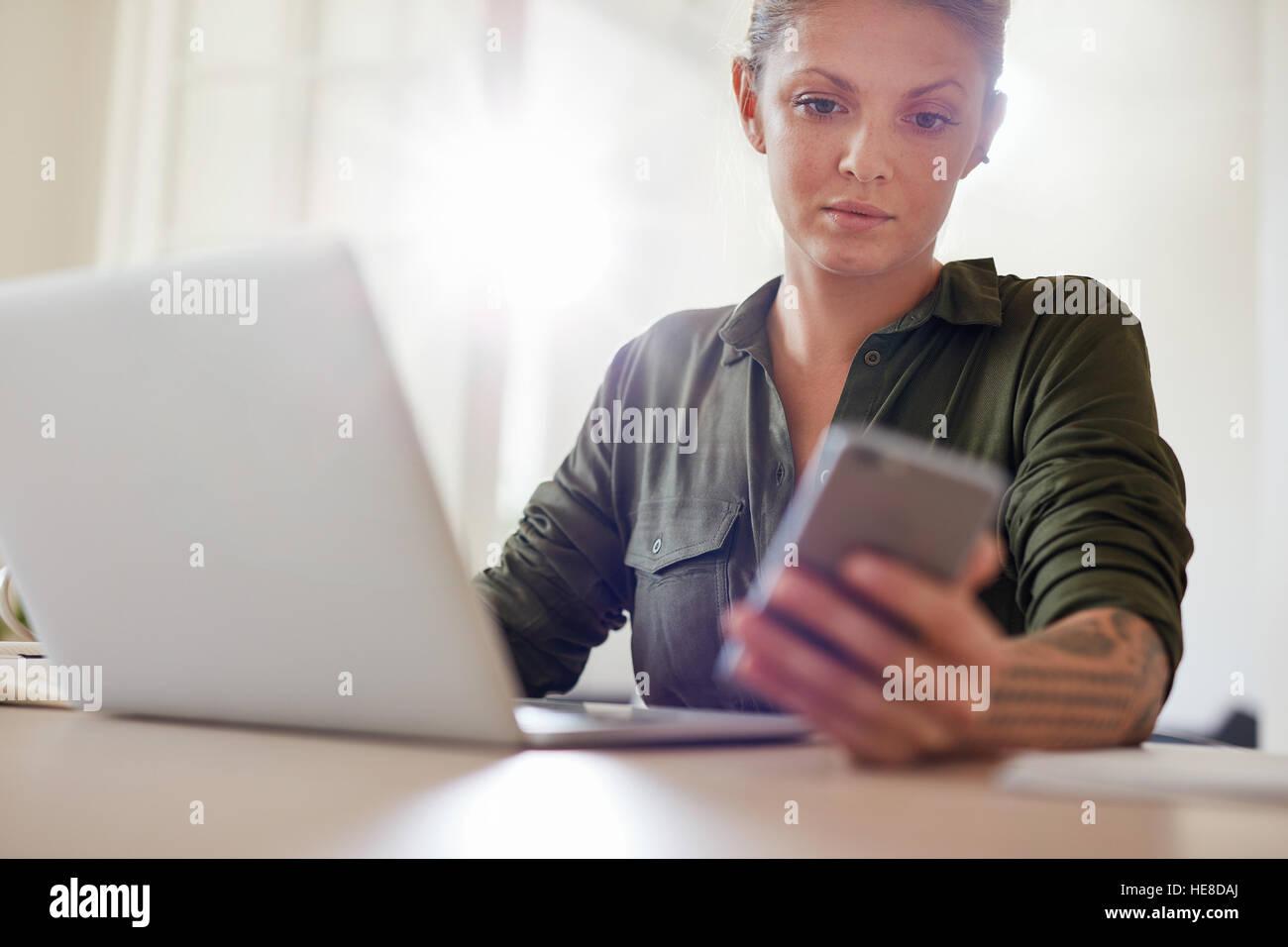 Schuss von attraktive junge Frau mit Laptop am Tisch sitzen und Lesen von SMS auf seinem Handy Stockbild