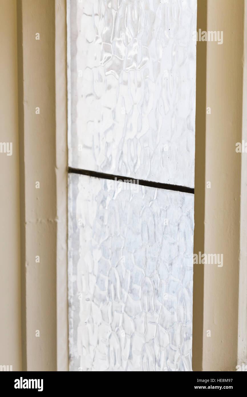 Weiß lackiertes Fensterrahmen mit strukturierten Ornamentglas und ...