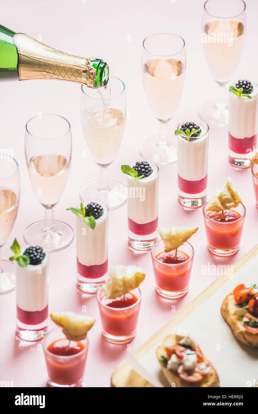 Verschiedene Snacks, Brushettas, Gazpacho Aufnahmen, Desserts, Champagner Gläser gießen Stockbild