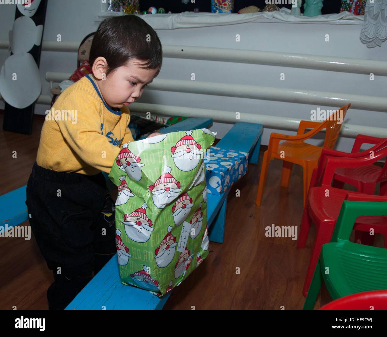 Ein kleiner Junge packt ein Geschenk im Vorschulalter Waisenhaus in ...