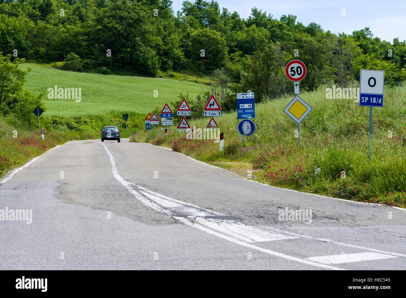 Typische grüne Toskana Landschaft im Val d'Orcia mit einer Straße flankiert bei vielen Verkehrszeichen Stockbild