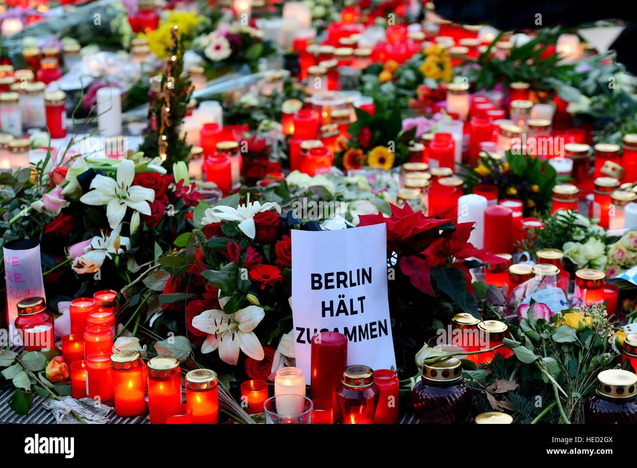 Berlin, Deutschland. 21. Dezember 2016. Passanten haben Kerzen und Blumen auf dem Gelände des Angriffs in der Stockbild