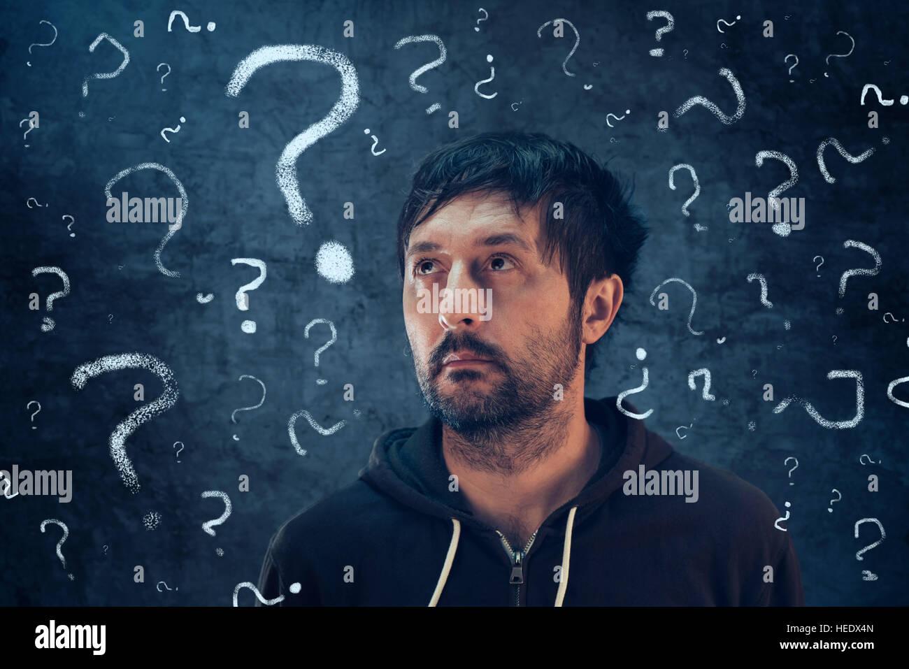 Verwirrten Mann mit so vielen Fragen, die auf der Suche nach der Antwort auf seine Probleme Stockbild