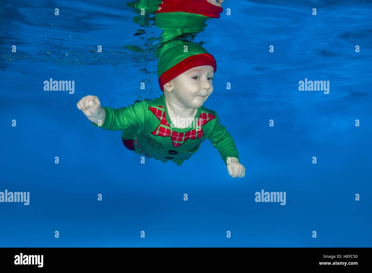 Ein kleiner Junge verkleidet als Weihnachtsmann Helfer unter Wasser ...