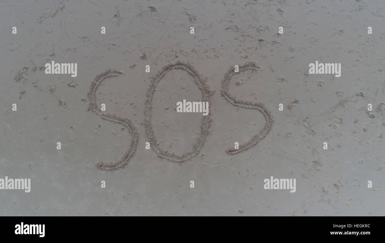 Ansicht von oben Foto von SOS in Sand am tropischen Strand geschrieben. Konzept-Foto der Hilfe Notfall Verzweiflung Stockfoto