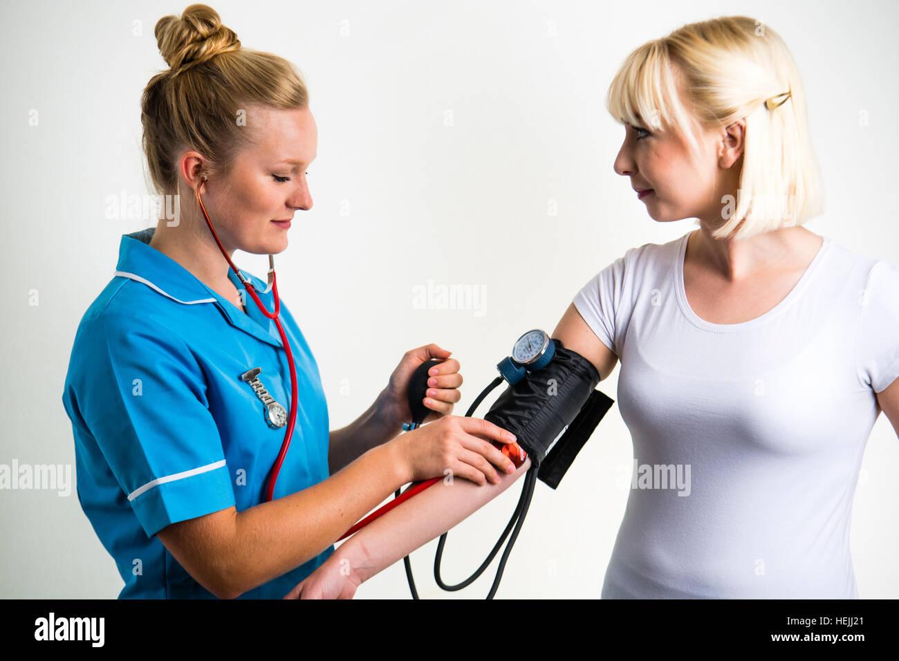 UK Health Care Professionals: A National Health Service (NHS) Frau Krankenschwester, die ein Patient Blutdruckmessung Stockbild
