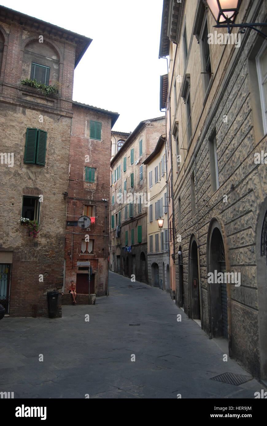 Jugendliche Frau Sitzt Alleine Auf Einer Mauer Mit Gekreuzten Beinen in Einer Gasse in der Altstadt von Siena, Toskana, Stockbild