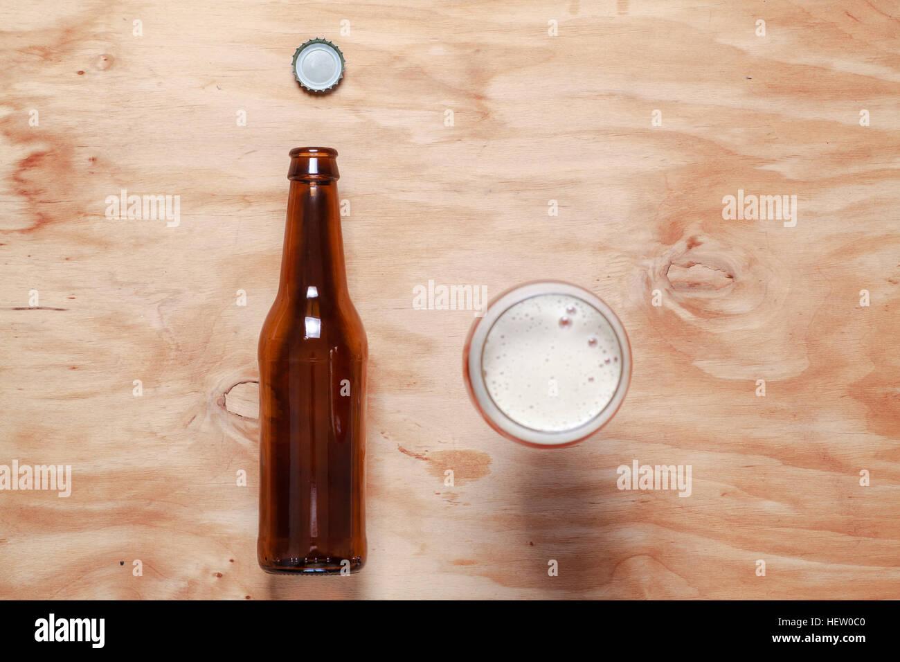 Glas voller bernsteinfarbene Bier und eine Bierflasche auf einer strukturierten Holzoberfläche Stockbild