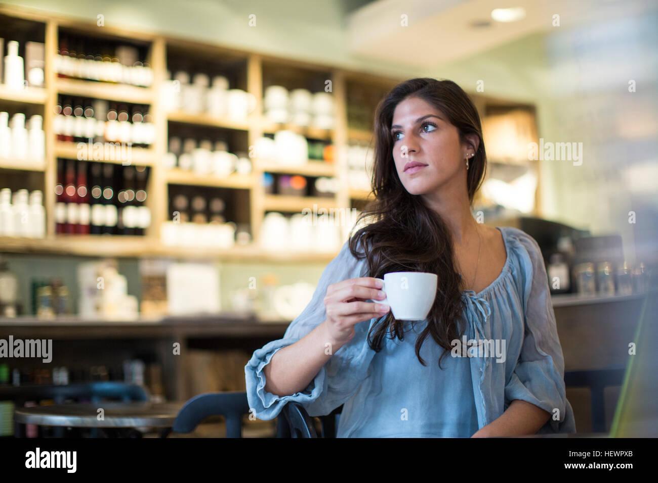 Junge Frau sitzt im Café suchen seitwärts Stockbild