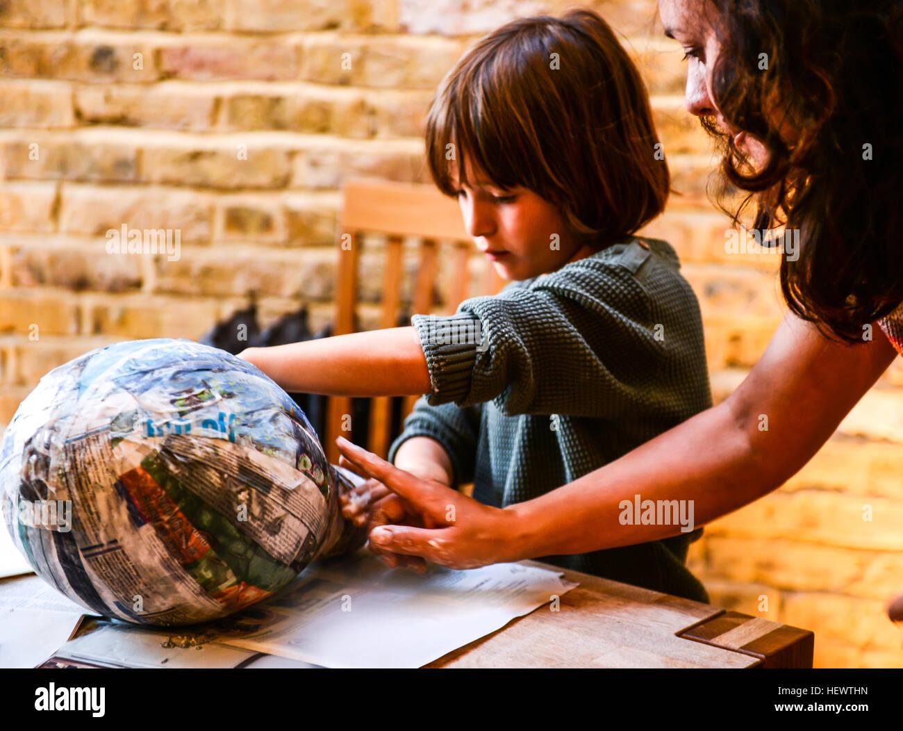 Kind und Mutter spielen mit papier mache Stockbild