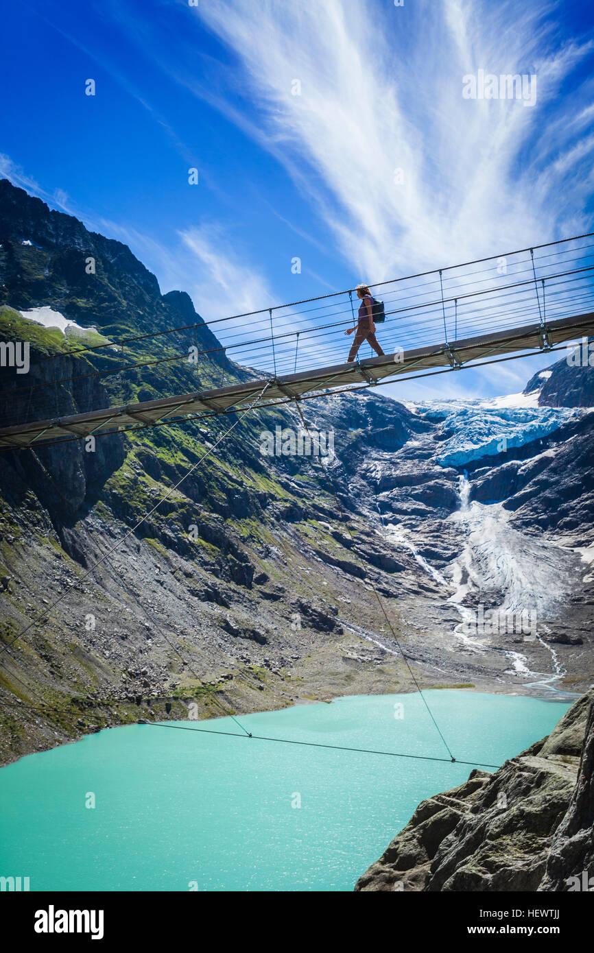 Touristen, die Überquerung der Brücke Trift, Schweiz Stockbild