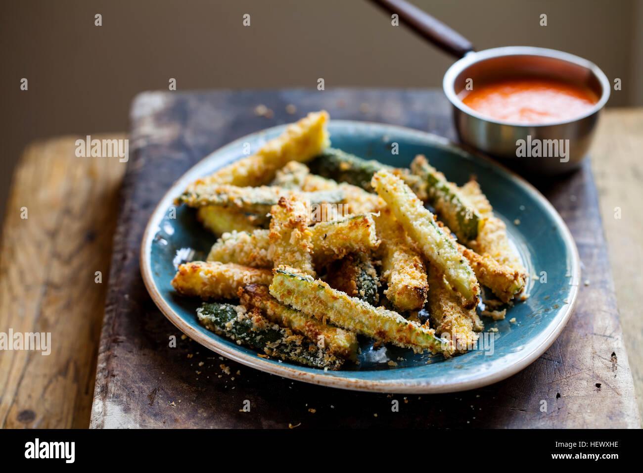 Zucchini-Brände mit gebratenem Paprika und Tomaten sauce Stockbild
