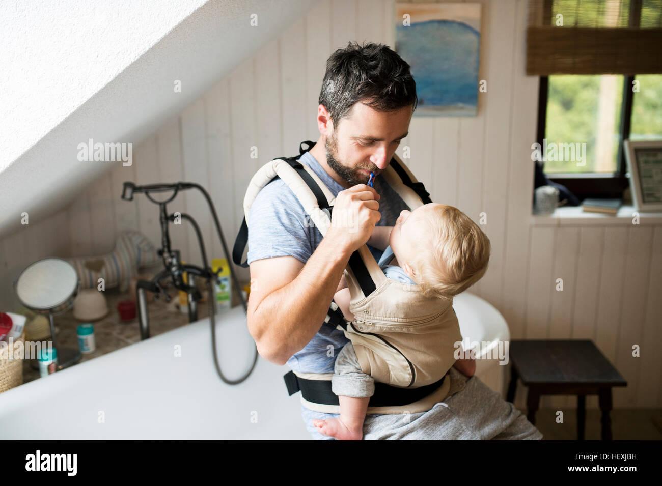 Vater mit Baby im Tragetuch, seine Zähne zu putzen Stockfoto
