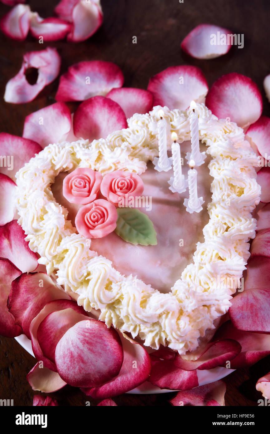 Herzförmigen Kuchen Mit Marzipanrosen Und Kerzen Auf Einem Bett Aus  Rosenblüten